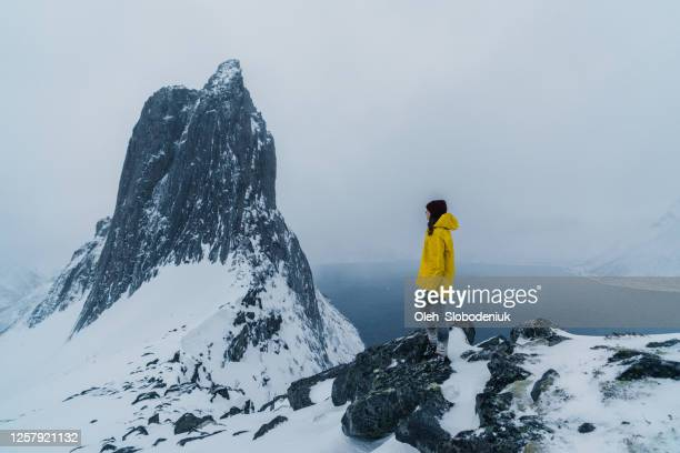 woman standing near  segla mountain  in norway in winter - scandinavia stock pictures, royalty-free photos & images