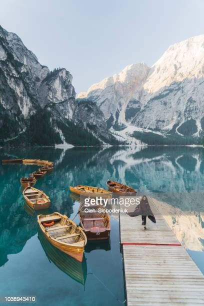 woman standing near the lake lago di braies  in dolomites - pragser wildsee stock pictures, royalty-free photos & images