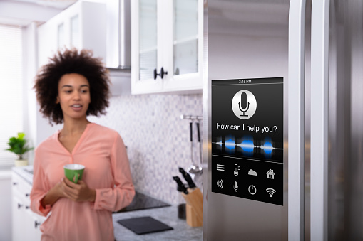 Woman Standing Near The Refrigerator With Voice Recognition 1093972270