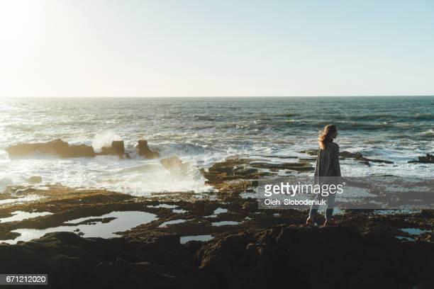 Femme debout près de la mer au Maroc