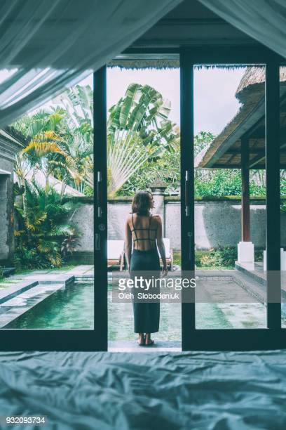 Woman standing near the swimming pool on villa