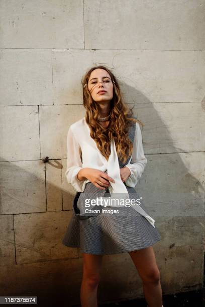 woman standing near the wall in a short skirt - legs and short skirt sitting down stock pictures, royalty-free photos & images