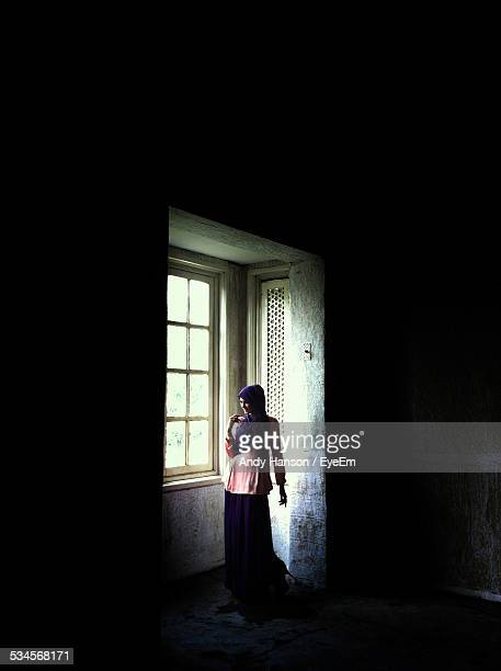 Woman Standing Near Window At Home