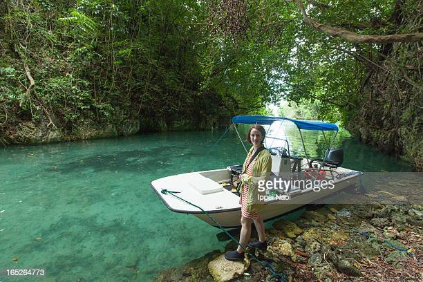 Woman standing next to a boat floating in a lagoon