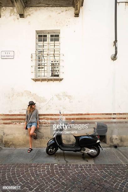 a woman standing next to a vespa - cultura italiana fotografías e imágenes de stock