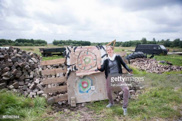 Woman standing next to her bow and arrow target with pride
