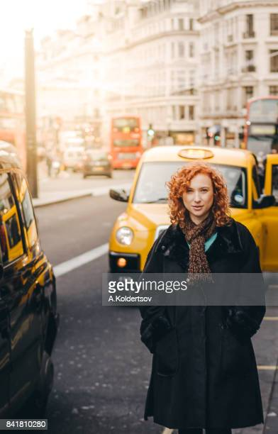 Woman standing next to London taxi during sunset