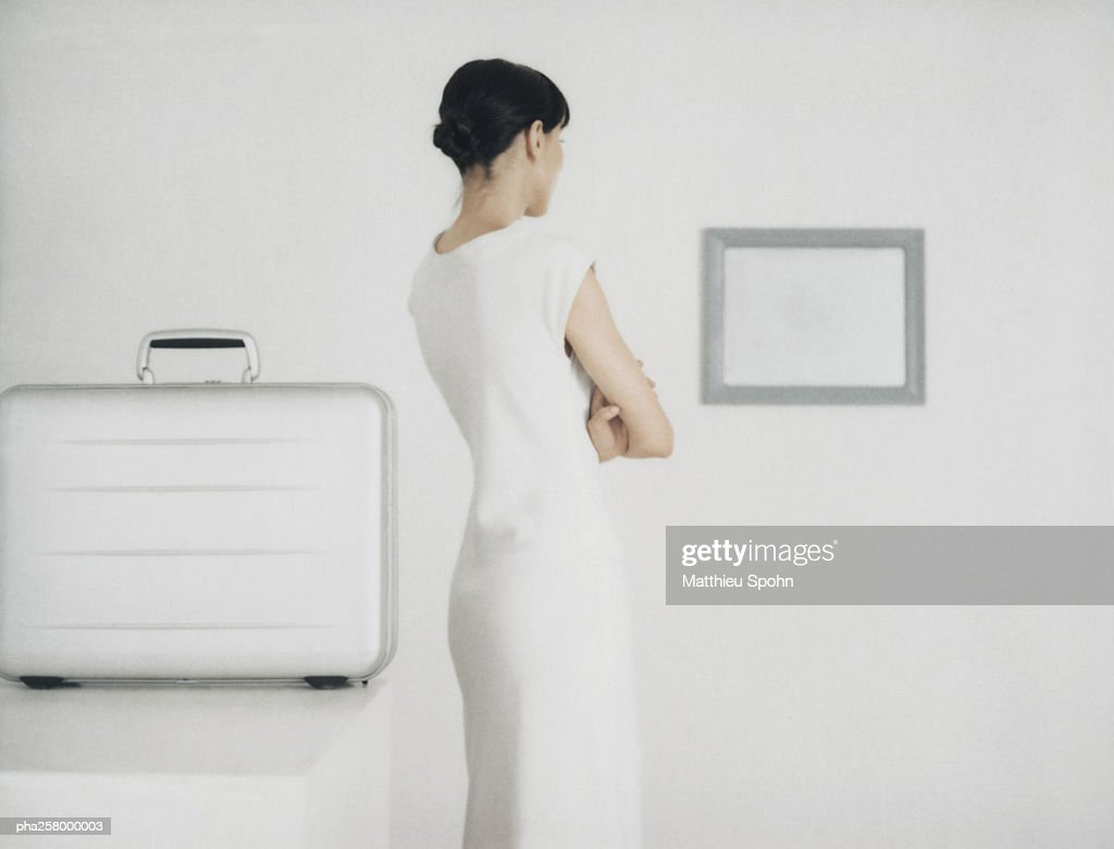 Woman standing next to table with metallic briefcase looking toward frame on wall : Stockfoto