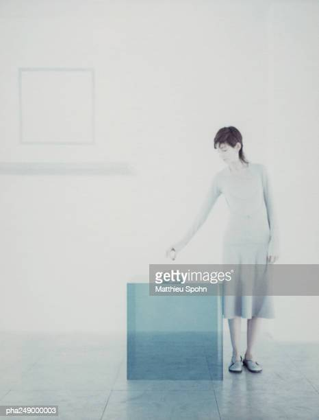 Woman standing next to translucent cube
