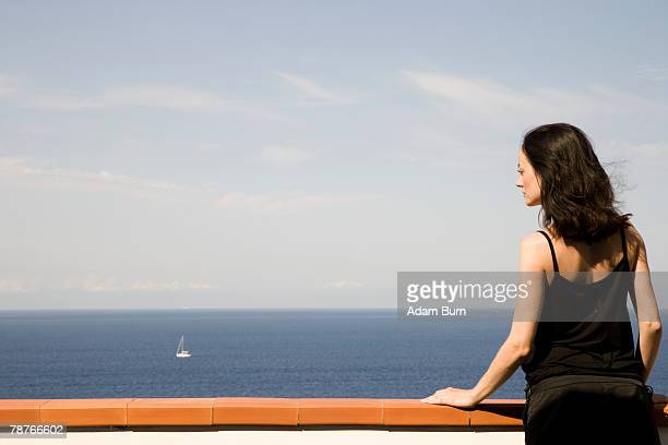 A woman standing on a balcony looking out to sea