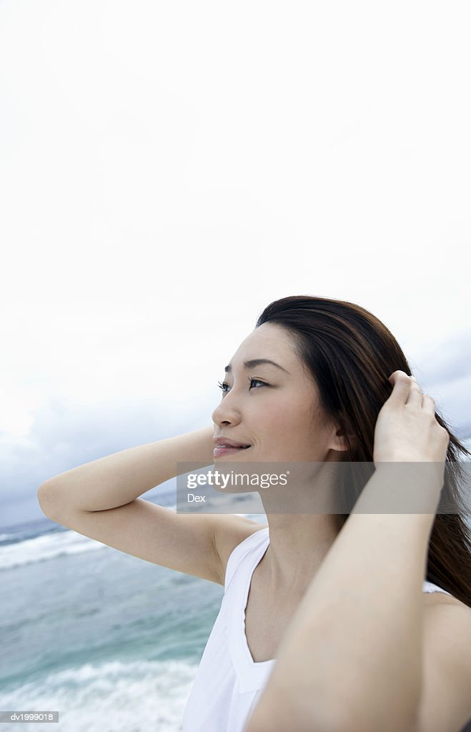 Woman Standing on a Beach Looking Up : Stock Photo