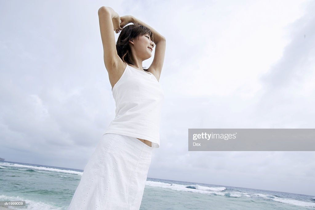 Woman Standing on a Beach With Her Arms Up : Stock Photo