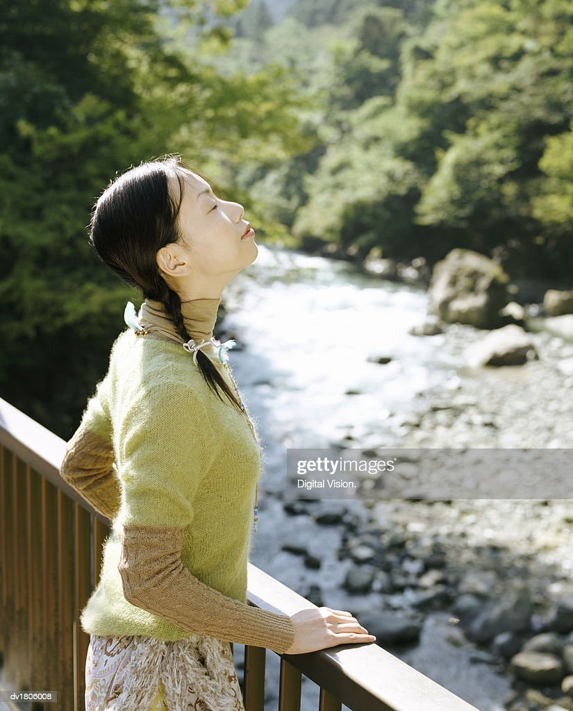 Woman Standing on a Bridge over a River with Her Eyes Closed and Inhaling : Stock Photo