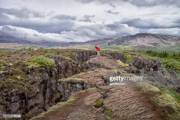 woman standing on a cliff edge looking at rift valley, thingvellir national park, iceland - tectonic stock photos and pictures