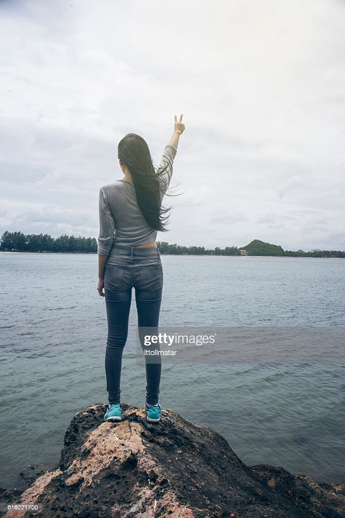 Woman standing on a cliff hill top,fighting or winner : Stock Photo