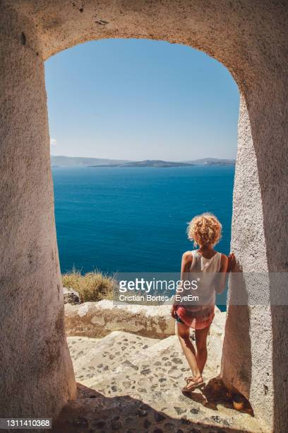woman standing on a covered footpath by the sea - bortes stock pictures, royalty-free photos & images