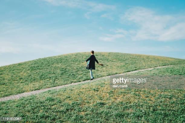 丘の上に立っている女性。 - 雰囲気 ストックフォトと画像