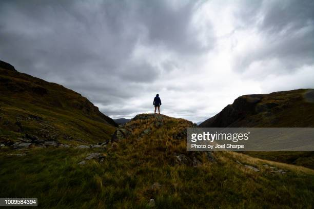 a woman standing on a hilly moor with a storm in the distance - heather storm stock photos and pictures