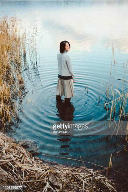 Une femme debout sur un lac.