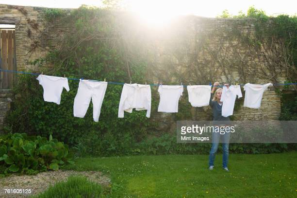 Woman standing on a lawn in a garden, hanging up laundry on washing line.