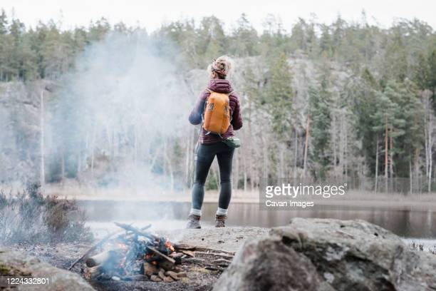 woman standing on a rock by a campfire whilst hiking in sweden - sweden stock pictures, royalty-free photos & images