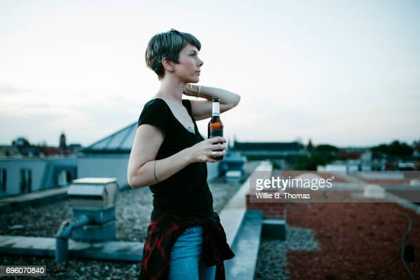 A Woman Standing On A Rooftop Enjoying A Beer