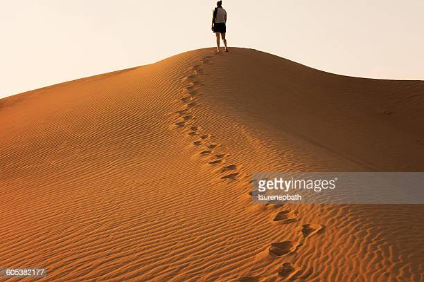 Woman standing on a sand dune in the desert, Dubai, UAE