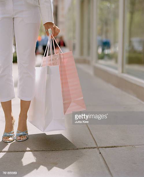Woman standing on a sidewalk and carrying shopping bags
