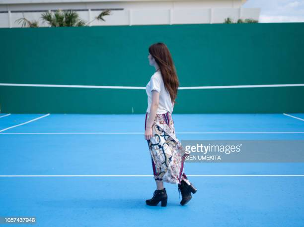 a woman standing on a tennis court - 後ろ姿 ストックフォトと画像