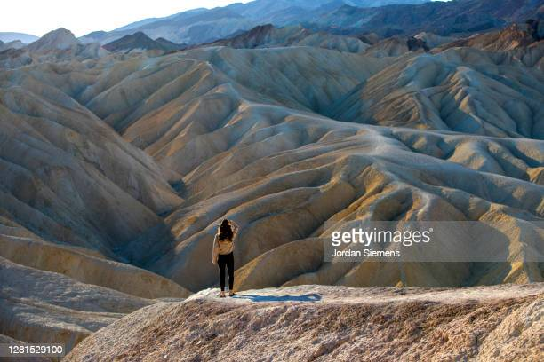 a woman standing on a viewpoint in death valley. - great basin stock pictures, royalty-free photos & images