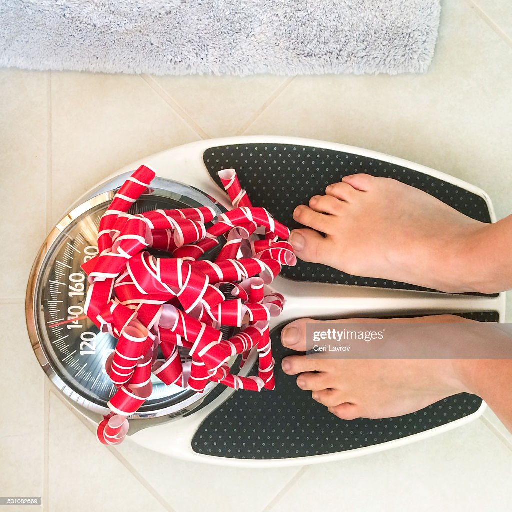 Woman standing on a weight scale with a bow on it : Stock Photo
