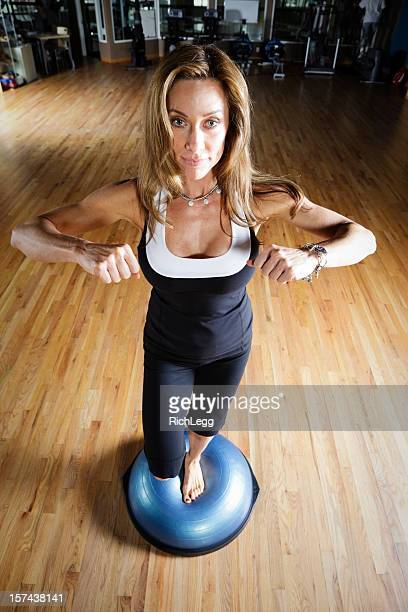 woman standing on balance ball in health club - cleavage stock pictures, royalty-free photos & images
