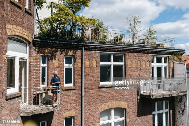 woman standing on balcony of brick house - balcony stock pictures, royalty-free photos & images