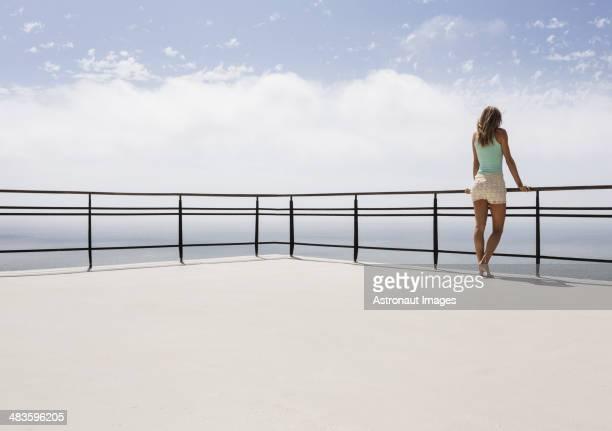 femme debout sur le balcon avec vue sur l'océan - garde corps photos et images de collection