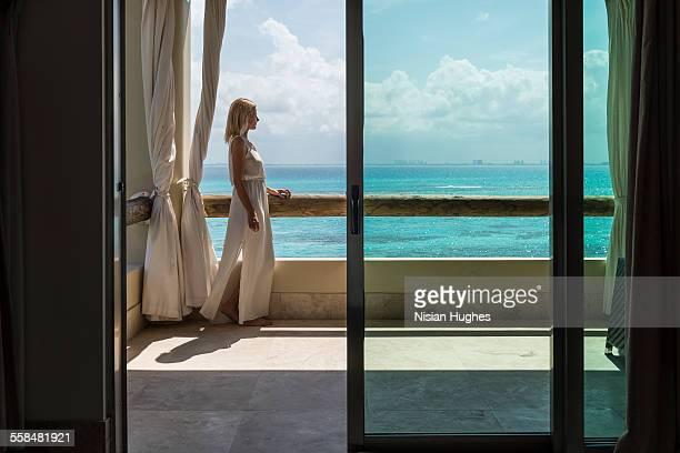 woman standing on balcony overlooking ocean - mujeres fotos stock-fotos und bilder