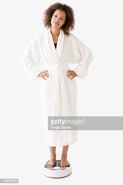 woman standing on bathroom scales - bathrobe stock pictures, royalty-free photos & images