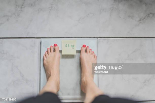 Woman standing on bathroom scales with sticky note of ideal weight