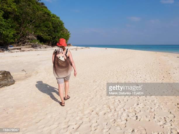 woman standing on beach against sea - marek stefunko stock pictures, royalty-free photos & images
