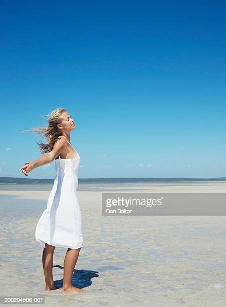 Woman standing on beach, arms outstretched, eyes closed, side view