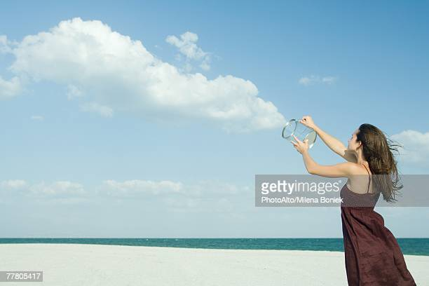 woman standing on beach, holding up clear container, releasing clouds, optical illusion - optical illusion stock photos and pictures