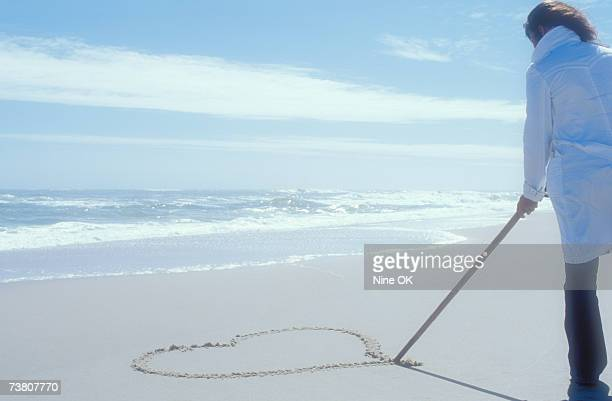 Woman standing on beach in winter, drawing heart in sand with stick, rear view
