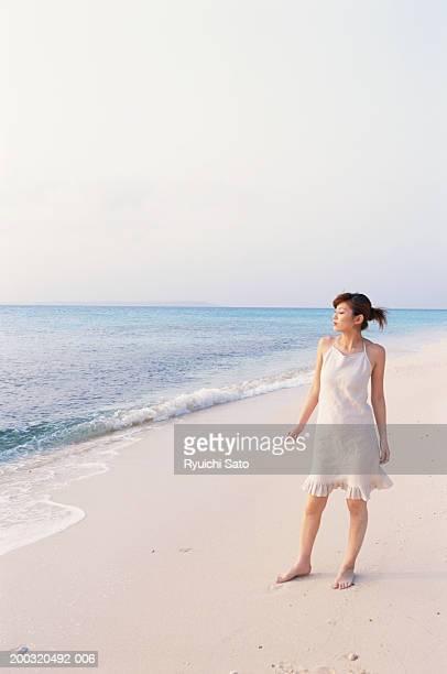 Woman standing on beach, looking away