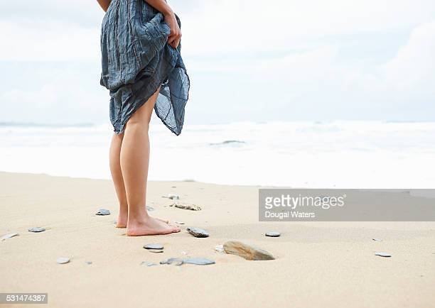Woman standing on beach looking out to sea