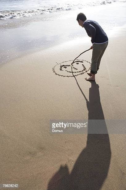 Woman standing on beach, making face shape in sand with stick, side view