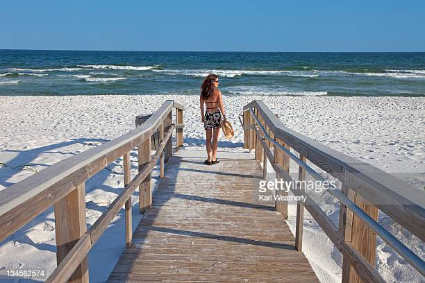 woman standing on beach ramp - pensacola beach stock pictures, royalty-free photos & images