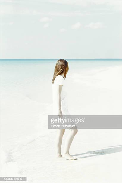 Woman standing on beach, rear view