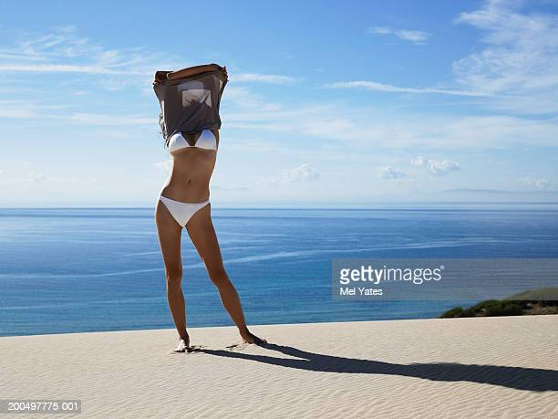 Woman standing on beach taking off dress over head