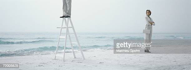 woman standing on beach with arms crossed, looking toward man standing on ladder - step ladder stock pictures, royalty-free photos & images