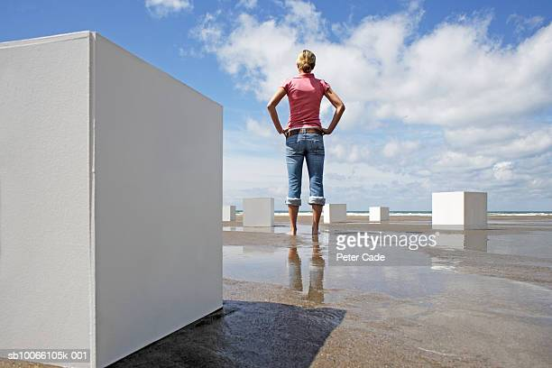 woman standing on beach with white boxes around, rear view - rolled up pants stock pictures, royalty-free photos & images