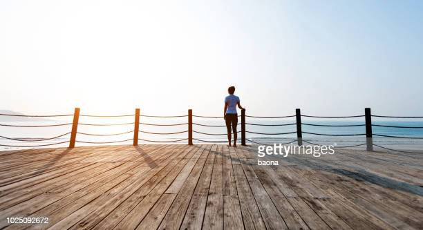 woman standing on boardwalk at the beach - pier stock pictures, royalty-free photos & images
